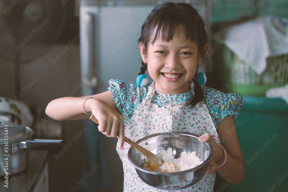 Fototapeta Little Child girl  wear apron and learning about cooking lunch in a kitchen.Vintage style