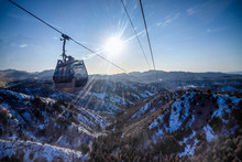 The Cable Car Is Going Up The Mountain In The Winter, Beautiful Sunlight.