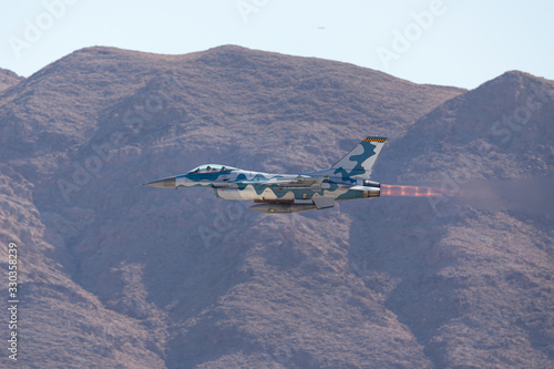Canvas Print F-16 Fighting Falcon in the Aggressor color scheme  against the Nevada hills, wi