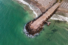 Aerial View Of A Concrete Pier On Sea Shore With Wave Breaking Stones.