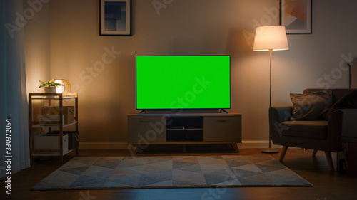 Fototapeta Shot of a TV with Horizontal Green Screen Mock Up. Cozy Evening Living Room with a Chair and Lamps Turned On at Home. obraz