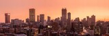 Fototapeta Miasto - A beautiful and dramatic panoramic photograph of the Johannesburg city skyline, taken on a golden evening after sunset.