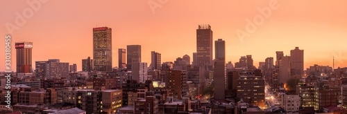 A beautiful and dramatic panoramic photograph of the Johannesburg city skyline, taken on a golden evening after sunset. #330380455