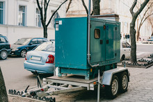 Mobile Moveable Gensets Portable Diesel Engine Power Electric Generator On A Trailer Stands On The City's Street. Green. Urban. Electricity. Power Supplier For Business. Outdoor. Sidewalk. Road. Wheel