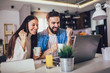 Leinwandbild Motiv Happy couple doing business together working at home on the laptop.