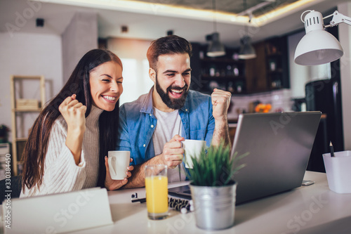 Happy couple doing business together working at home on the laptop Canvas Print