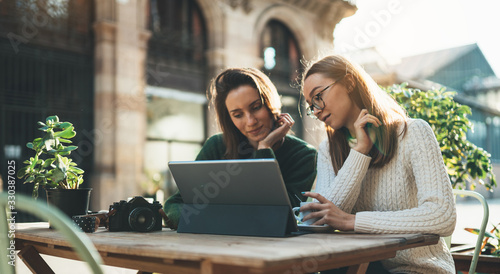 Girls drink coffee relax in cafe outdoor in europe city. Freelancer communicate on project, woman shopping online on wifi tablet. Working business process