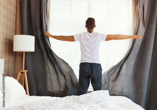 Photo Anonymous man pulling curtains in morning.
