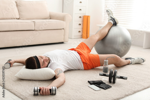 Lazy young man with sport equipment sleeping on floor at home Canvas Print