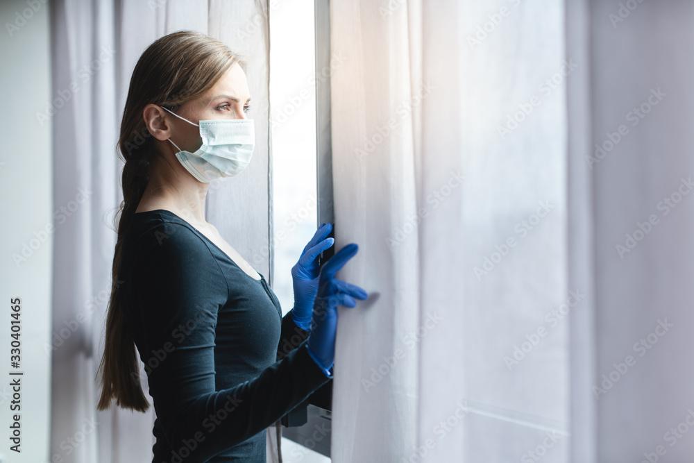 Fototapeta Bored woman in corona quarantine looking out of window