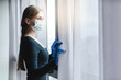 canvas print picture - Bored woman in corona quarantine looking out of window