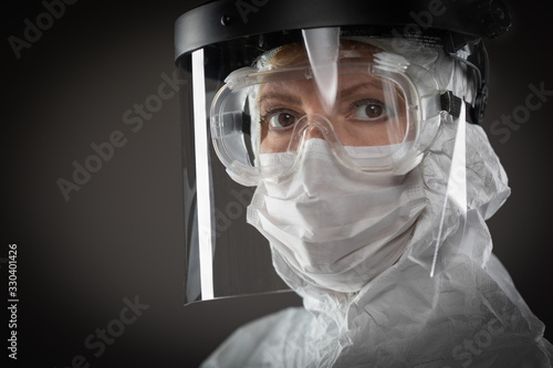 Fotografiet Female Medical Worker Wearing Protective Face Mask and Gear Against Dark Backgro