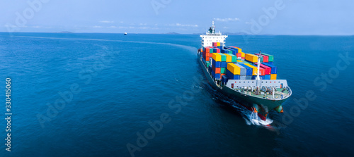 Fotografía Aerial infront of cargo ship carrying container and running for export  goods  from  cargo yard port to custom ocean concept freight shipping by ship