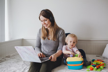 Young Caucasian Mother Blogger With Baby Working On Laptop From Home. Workplace Of Freelance Woman Student With A Kid Toddler. Stay At Home Single Mom Earning Money At Online Job.