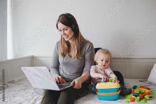 Valokuva Young Caucasian mother blogger with baby working on laptop from home