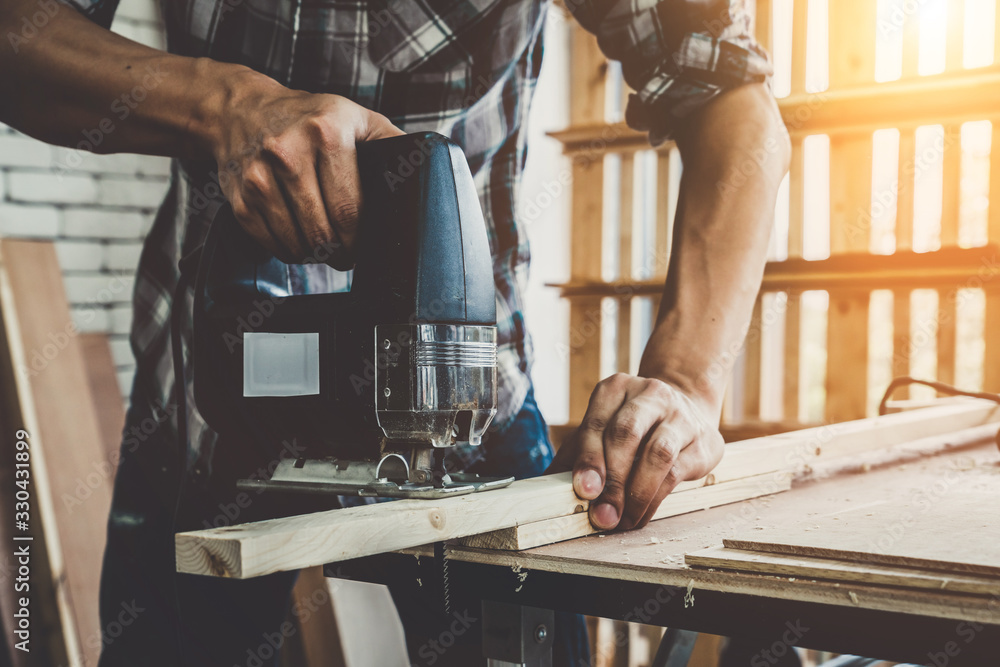 Fototapeta Carpenter working on wood craft at workshop to produce construction material or wooden furniture. The young Asian carpenter use professional tools for crafting. DIY maker and carpentry work concept.