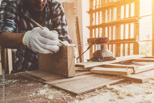 Carpenter working on wood craft at workshop to produce construction material or wooden furniture Fototapet