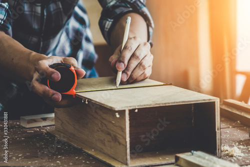 Obraz Carpenter working on wood craft at workshop to produce construction material or wooden furniture. The young Asian carpenter use professional tools for crafting. DIY maker and carpentry work concept. - fototapety do salonu