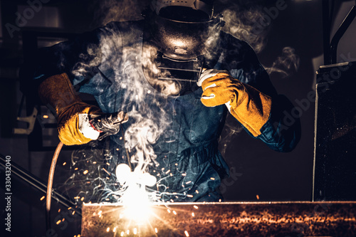 Leinwand Poster Metal welder working with arc welding machine to weld steel at factory while wearing safety equipment