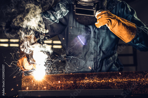 Fototapeta Metal welder working with arc welding machine to weld steel at factory while wearing safety equipment. Metalwork manufacturing and construction maintenance service by manual skill labor concept. obraz