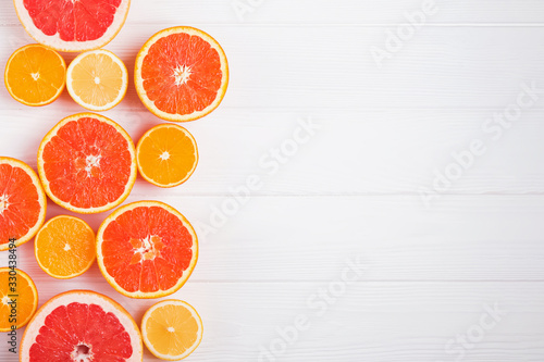 Fototapeta Flat lay composition with halves of different citrus fruits on white wooden background obraz