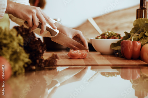 Fototapeta Unknown human hands cooking in kitchen. Woman slicing red tomatoes. Healthy meal, and vegetarian food concept obraz