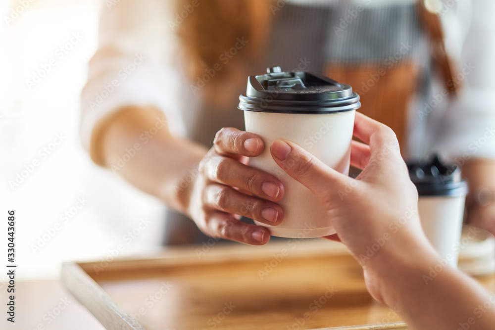 Fototapeta A waitress holding and serving paper cups of hot coffee to customer in cafe