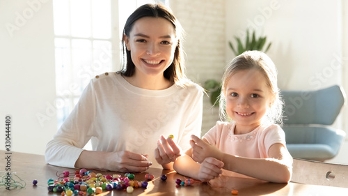 Head shot portrait smiling young mother sitting at table with adorable small daughter, creating handmade bracelets Canvas Print