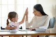 canvas print picture - Joyful small daughter giving high five to satisfied with homework results mother. Happy young mom teacher babysitter praising little preschool child girl for making right tasks, sitting at home.