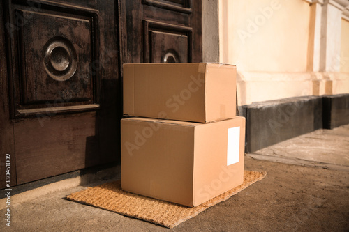 Delivered parcels on door mat near entrance - 330451009