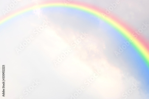 A rainbow in many clouds with sunlight on the sky.