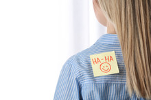 Woman With HA-HA Sticker On Back Against Light Background, Closeup. April Fool's Day