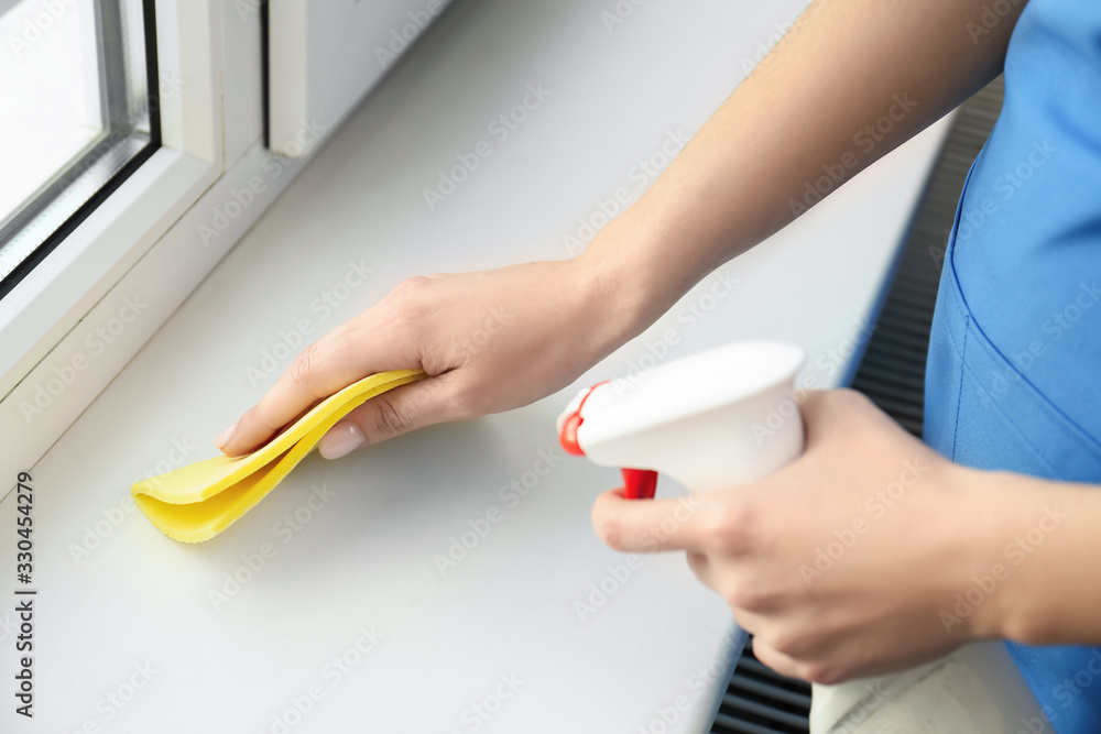 Fototapeta Woman cleaning window sill with rag and detergent indoors, closeup