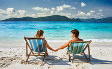 Couple In Loungers On A Beach ...