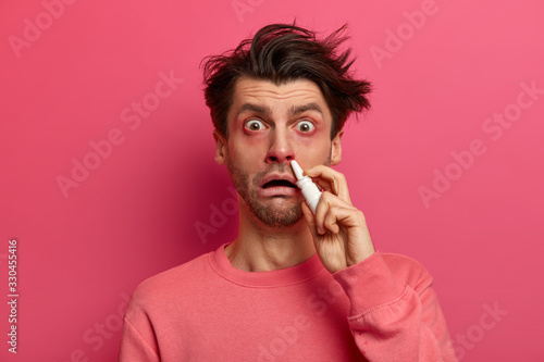 Vászonkép Shocked man has red swollen eyes, splashes nose drops, cures allergic rhinitis, has home treatment, stares at camera, poses against pink background drips medication inside