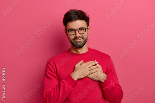 Grateful bearded man presses palms to heart, being moved and touched by pleasant Canvas Print