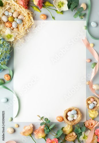 Fototapeta Happy Easter concept with easter eggs in nest and spring flowers. Easter background with copy space. Flat lay obraz