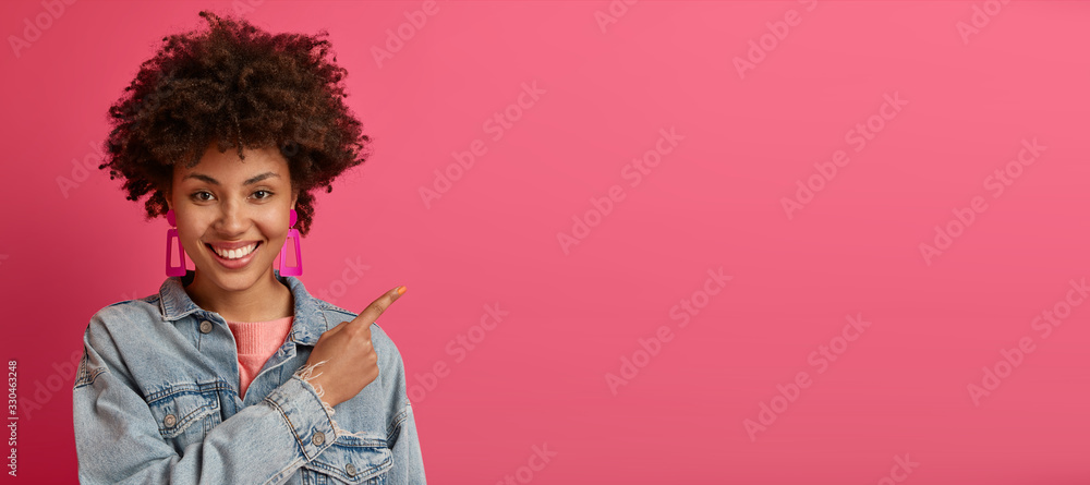 Fototapeta Horizontal shot of pleasant looking smiling female model indicates at copy space, advertises something nice and appealing, gives advice, wears fashionable denim jacket, isolated on pink background