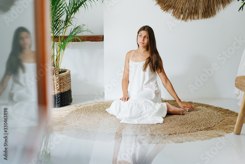 Relaxed emotionless young woman in a white dress posing in a tropical style room Slika na platnu