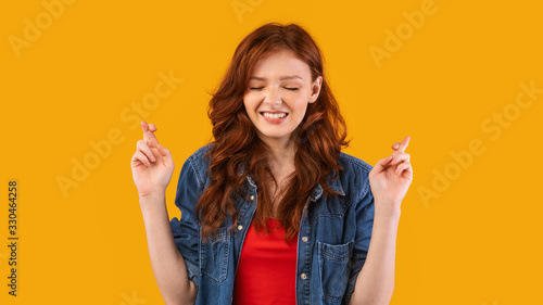 Fotografie, Tablou Girl Keeping Fingers Crossed Making Wish Posing Over Yellow Background