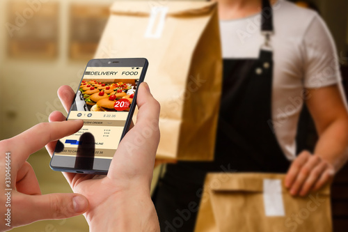 Fototapeta man holding touch phone with app delivery food screen obraz