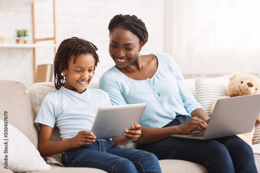 Fototapeta Afro mom and daughter doing school homework on sofa