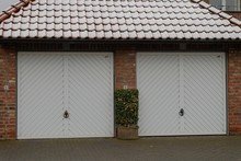Garages With White Windows And A Red Roof Covered In The Snow At Daytime