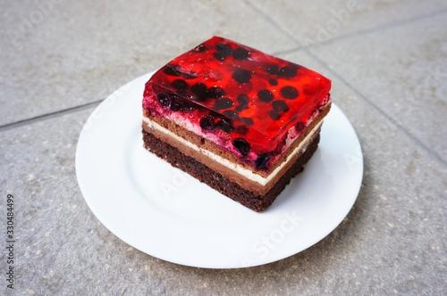 Photo Closeup shot of a raspberry cake piece eon the white plate