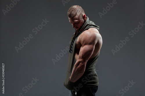 Fotografiet Athletic white man shows muscles side view against a dark background