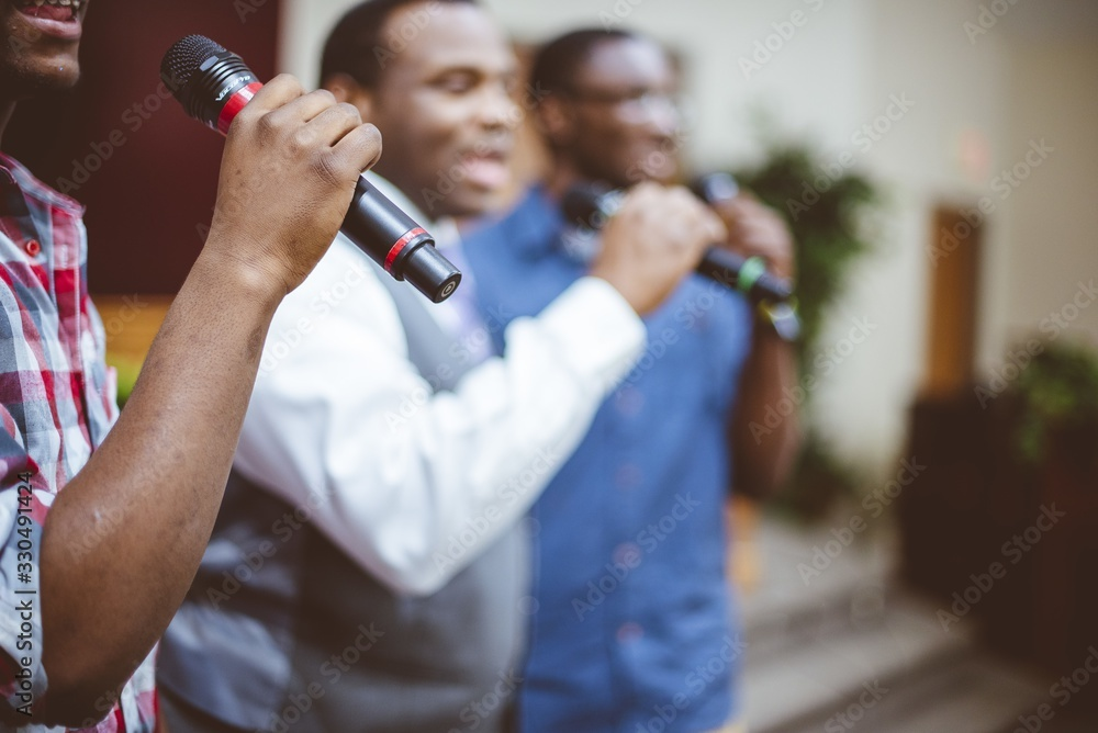 Fototapeta Group of African-American friends singing with microphones at the church
