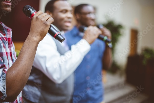 Group of African-American friends singing with microphones at the church