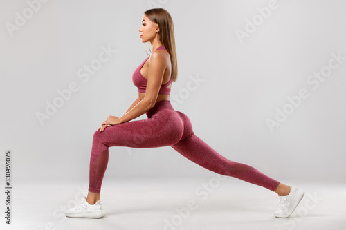 Fototapeta Fitness woman doing lunges exercises for leg muscle workout training. Active girl doing front forward one leg step lunge exercise, on the gray background obraz