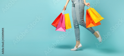Fotografía Beautiful young woman and shopping bags on blue background