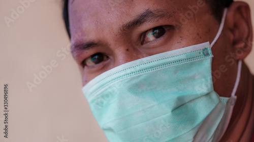 Asian man wearing a medical face mask to anticipate the spread of diseases caused by viruses, such as coronavirus or covid-19 and avian influenza, which become a world pandemic Wallpaper Mural